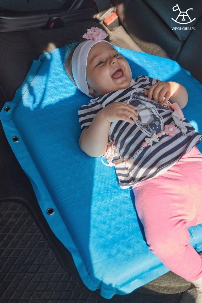dziewczynka leży na przewijaku podróżnym w samochodzie