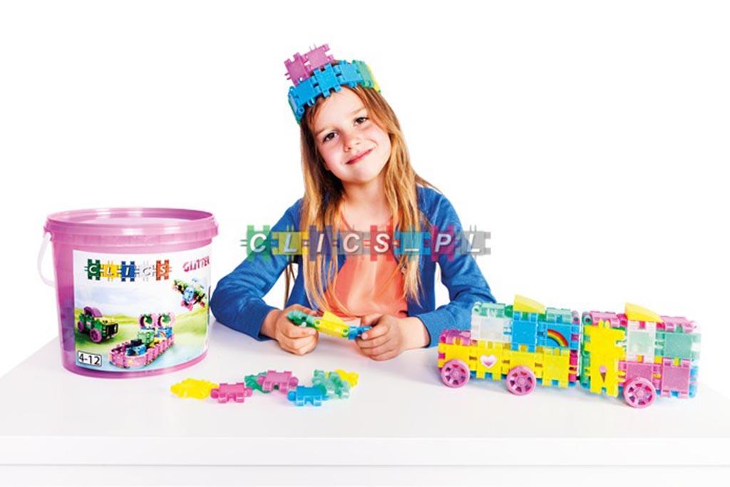 dziewczynka składająca brokatowe klocki