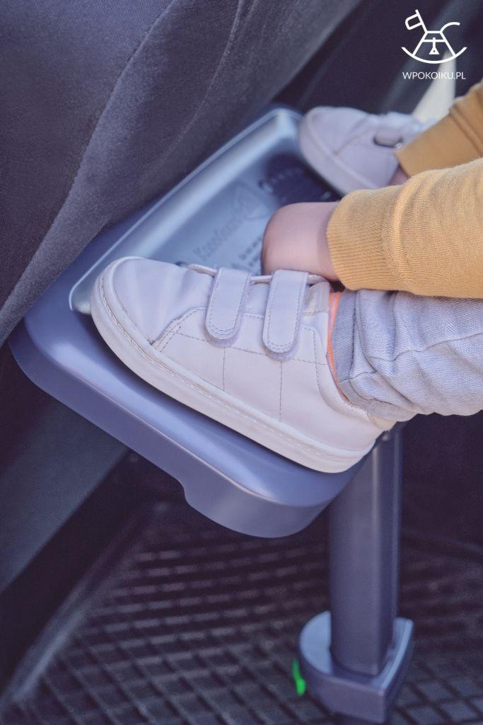 chłopiec trzyma stopy na podnóżku siedząc w foteliku