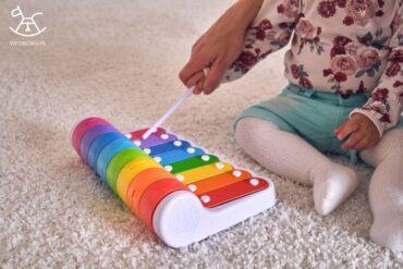 dziewczynka bawi się kolorowym pianinkiem