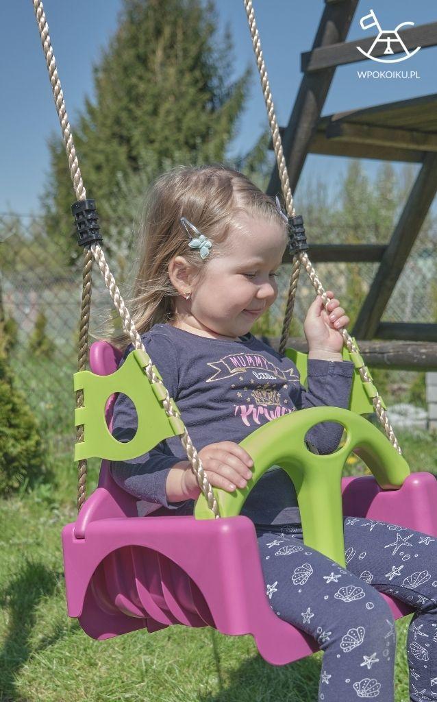 dziewczynka buja się na fioletowej huśtawce dla dzieci