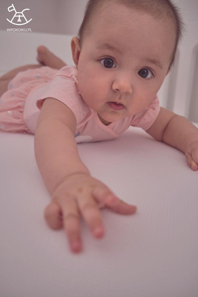 małe dziecko leżące na macie antypotowej i prześcieradle