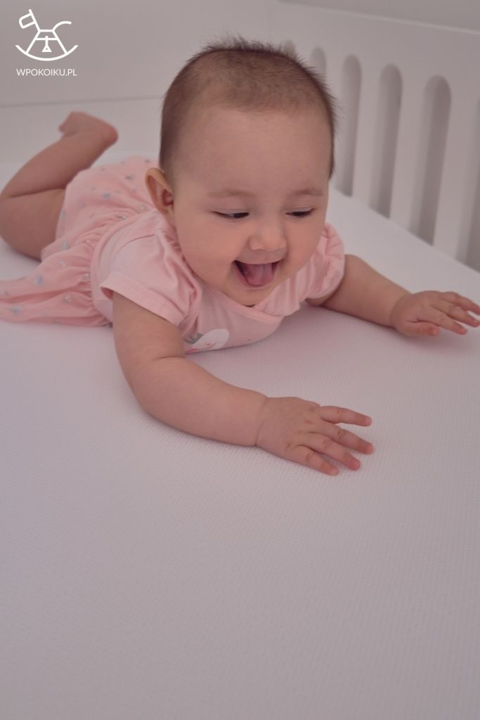 radosne małe dziecko leżące na macie antypotowej i przewiewnym prześcieradle