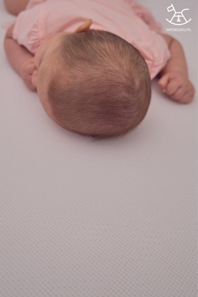 dziecko leżące na macie antypotowej i przewiewnym prześcieradle