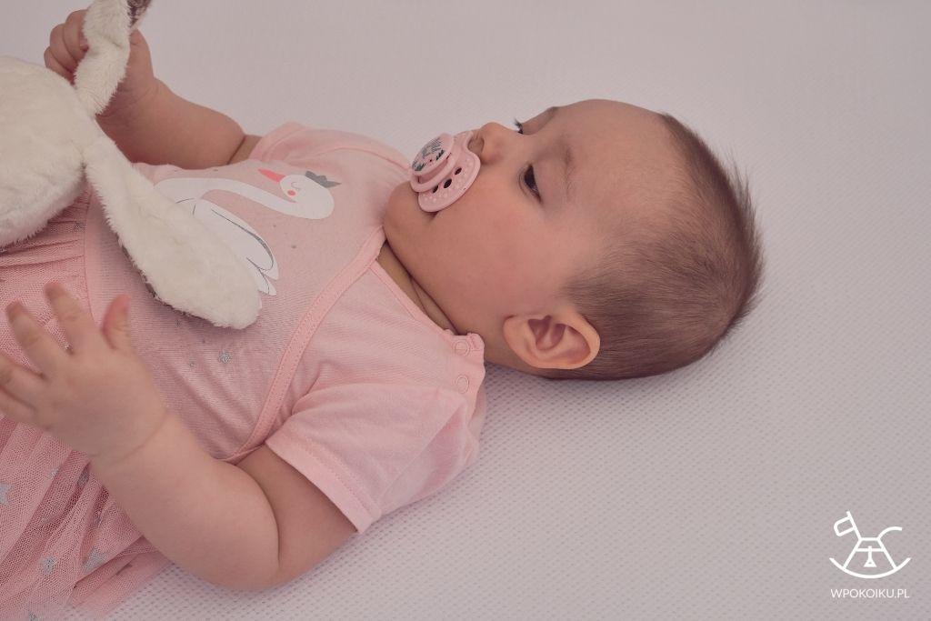 małe dziecko leżące na macie antypotowej i przewiewnym prześcieradle