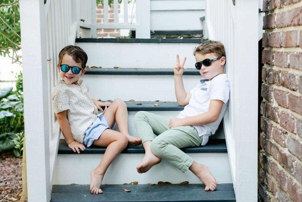 chłopcy w okularach przeciwsłonecznych siedzą na schodach przed domem