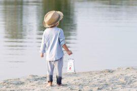 chłopczyk niosący przenośny nocnik nad jeziorem