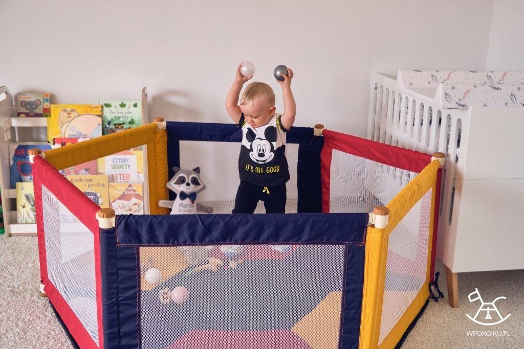 chłopiec bawi się piłkami w materiałowym kojcu