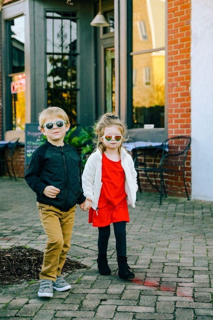 chłopiec i dziewczynka idą po chodniku trzymając się za rękę