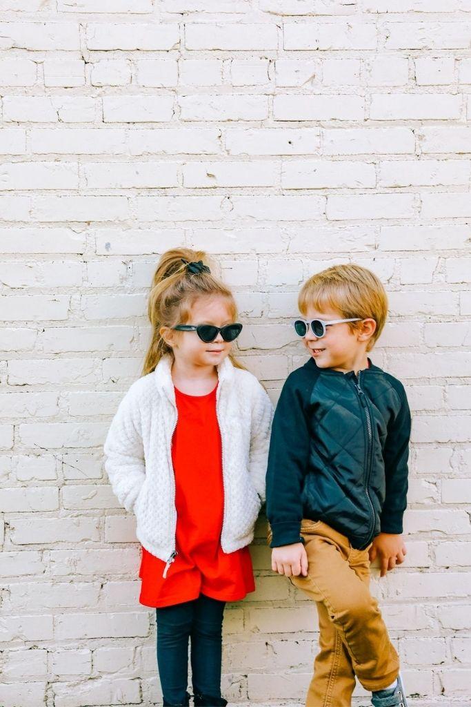 chłopiec i dziewczynka w okularach przeciwsłonecznych stoją opierając się plecami o biały mur