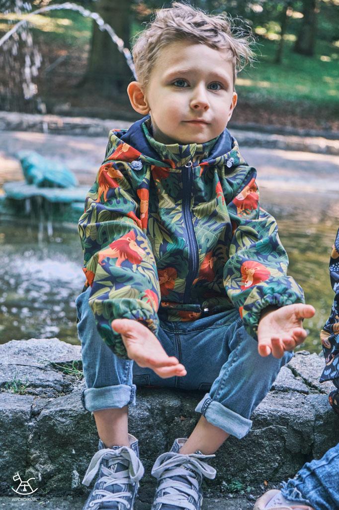 chłopiec siedzi na murku i wyciąga przed siebie ręce