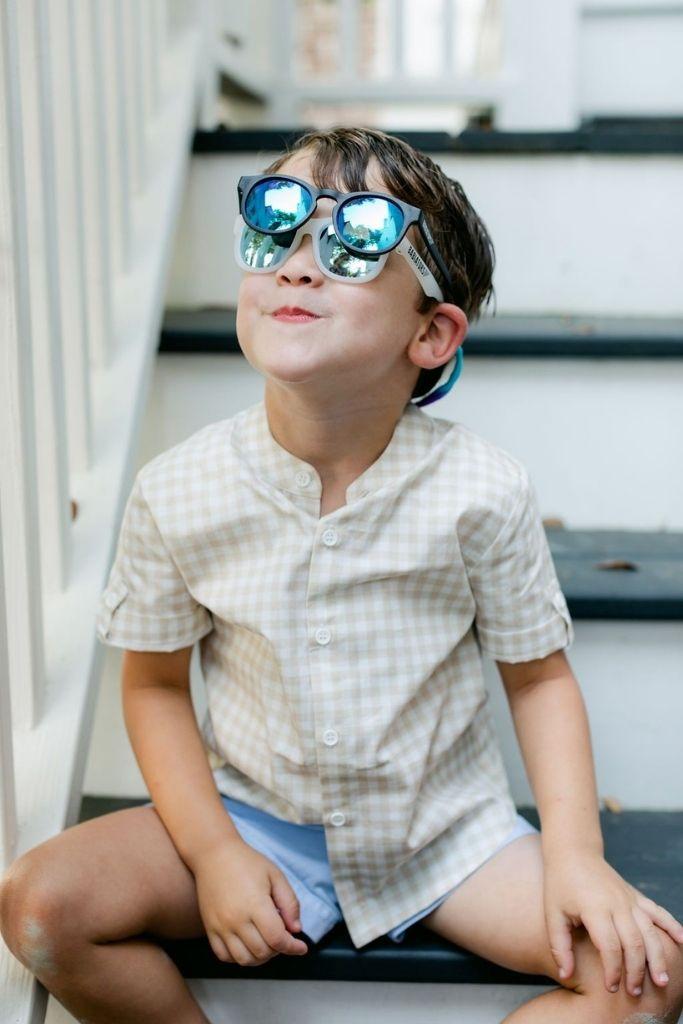 chłopiec siedzi na schodach z dwiema parami okularów na twarzy