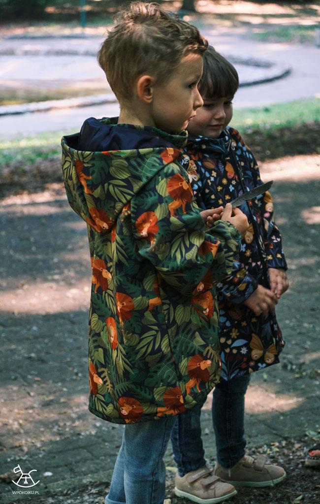 chłopiec stoi obrócony bokiem w kurteczce
