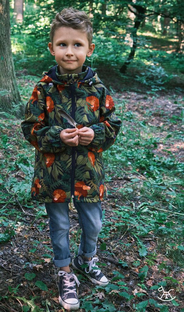 chłopiec trzyma piórko, które znalazł w parku