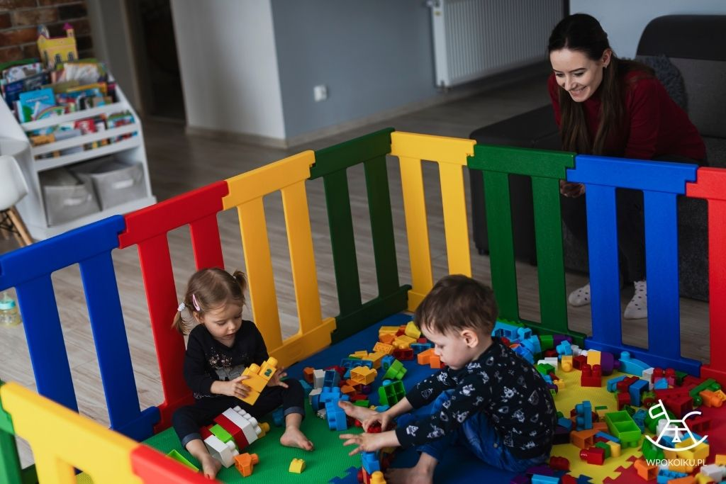 dzieci bawią się klockami w plastikowym kojcu z piankową matą