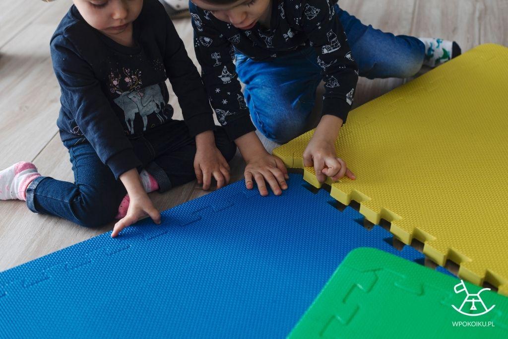 dzieci składają piankową matę puzzle