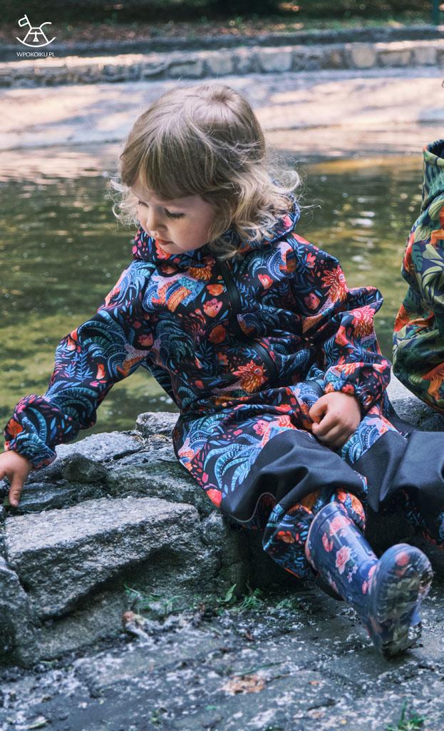 dziewczynka ogląda kamienie na murku