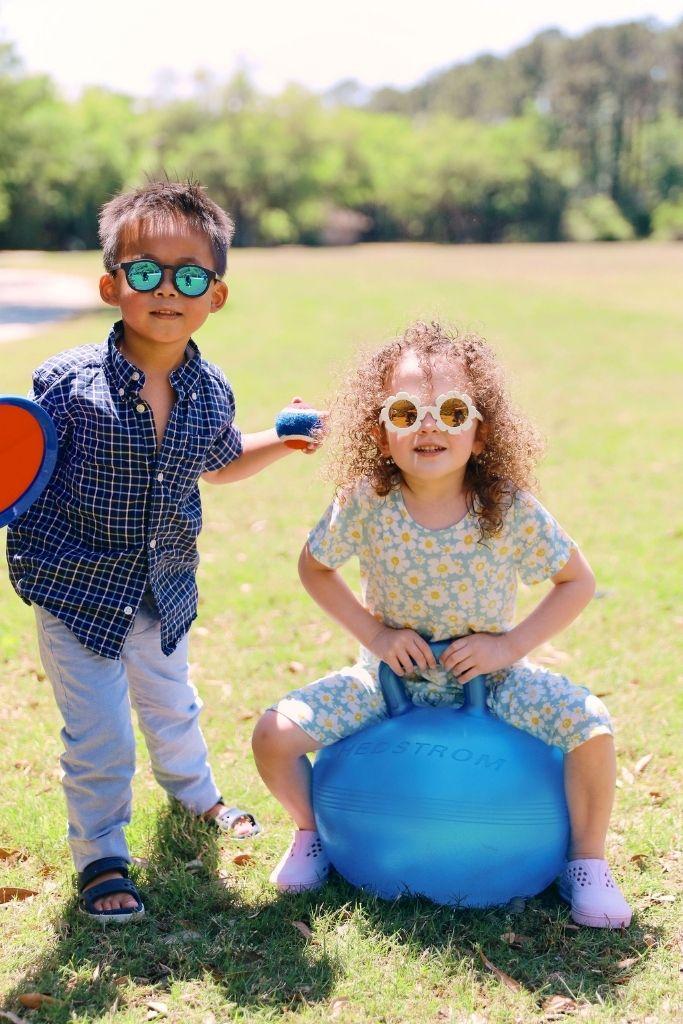 dziewczynka siedzi na piłce do skakania obok chłopca trzymającego piłkę