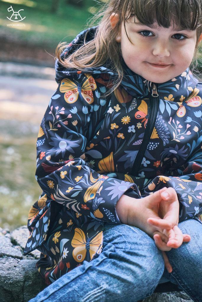 dziewczynka w kurtce typu parka siedzi na murku