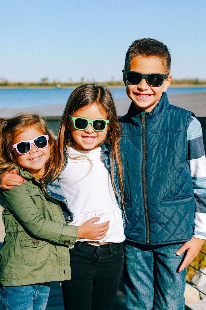 trójka dzieci pozuje razem nad wodą