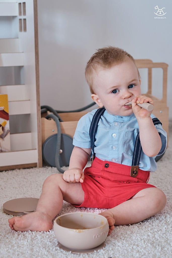 chłopczyk je mus owocowy z pomocą łyżeczki silikonowej