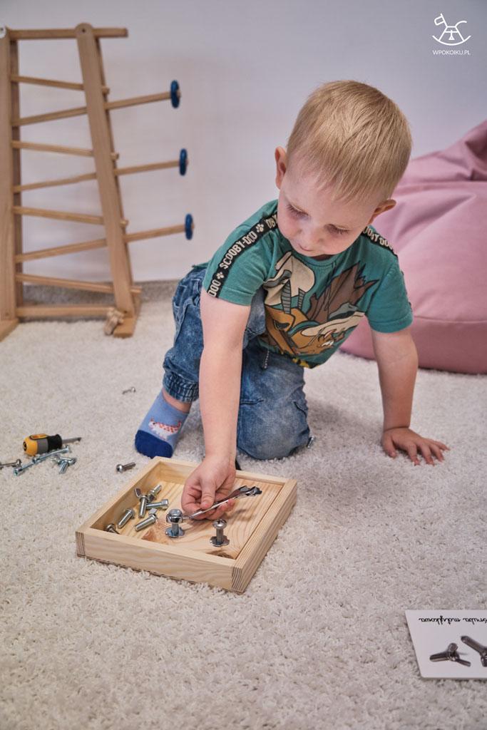 chłopczyk wkręca śrubki do drewnianej zabawki