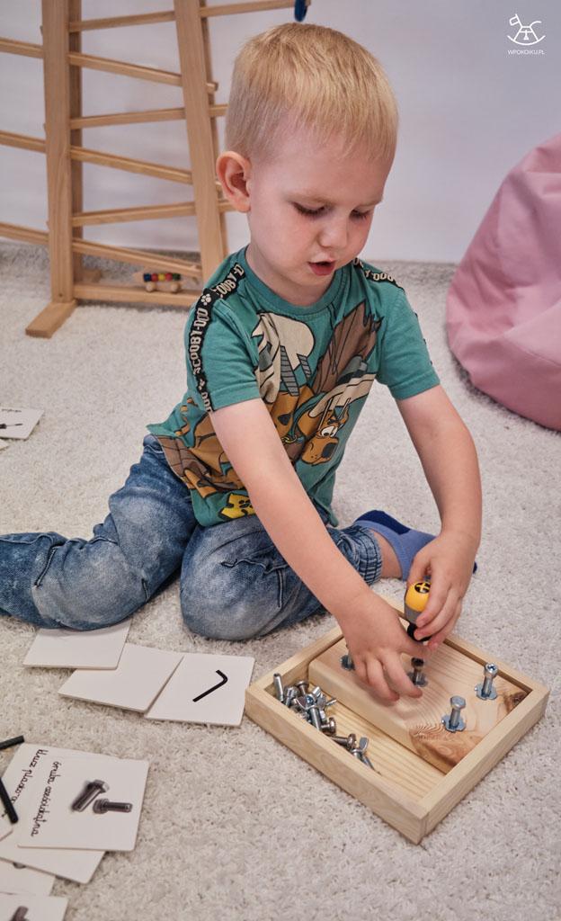 chłopiec próbuje wkręcić śrubkę śrubokrętem do drewnianej deseczki