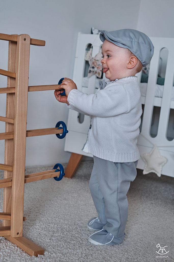 chłopiec radośnie bawi się drewnianą zabawką