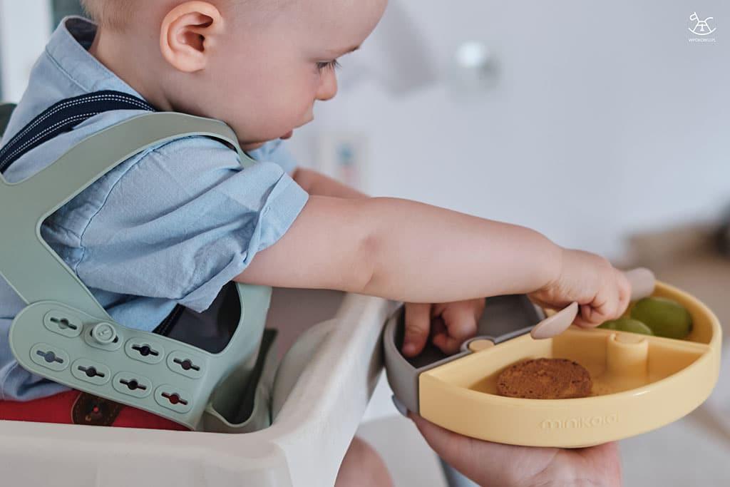 chłopiec sięga po przekąski z talerzyka