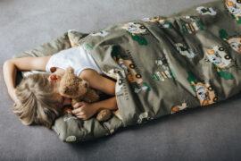 chłopiec śpi w ocieplanym śpiworze z motywem safari