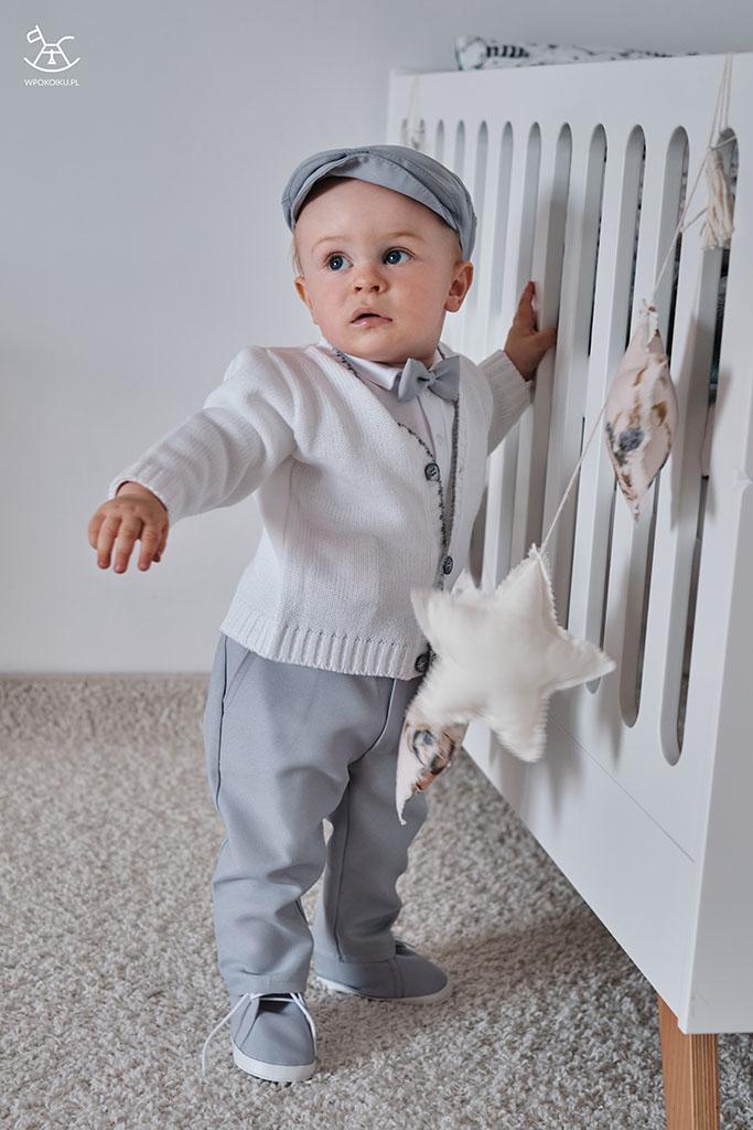 chłopiec stoi oparty o łóżeczko w komplecie biało szarym