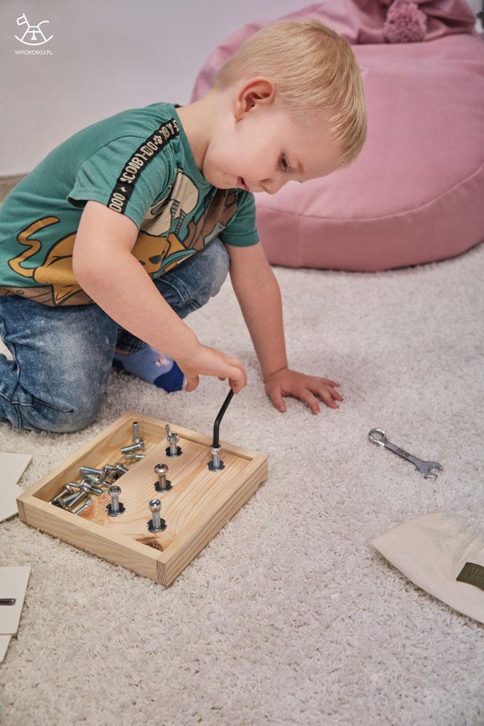 chłopiec wkręca śrubę kluczem imbusowym