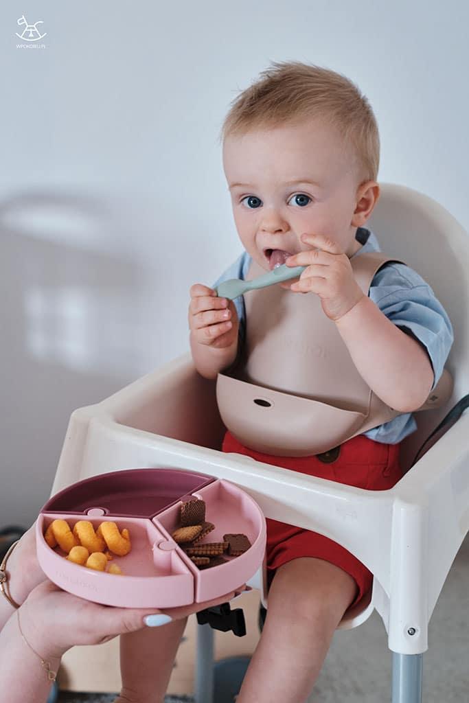 dziecko je przekąski z silikonowego talerzyka