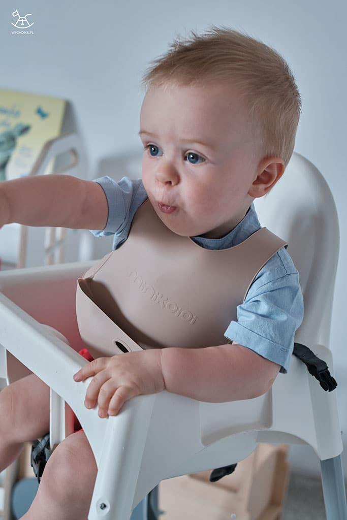 dziecko w krzesełku do karmienia z ubranym silikonowym śliniakiem
