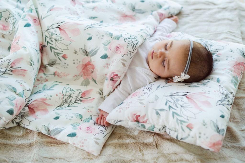dziewczynka śpiąca w bambusowej pościeli w magnolie
