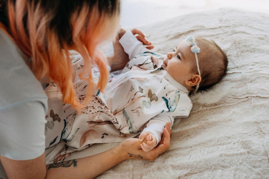 mama kładzie córeczkę do spania w śpiworku bambusowym z motywem safari