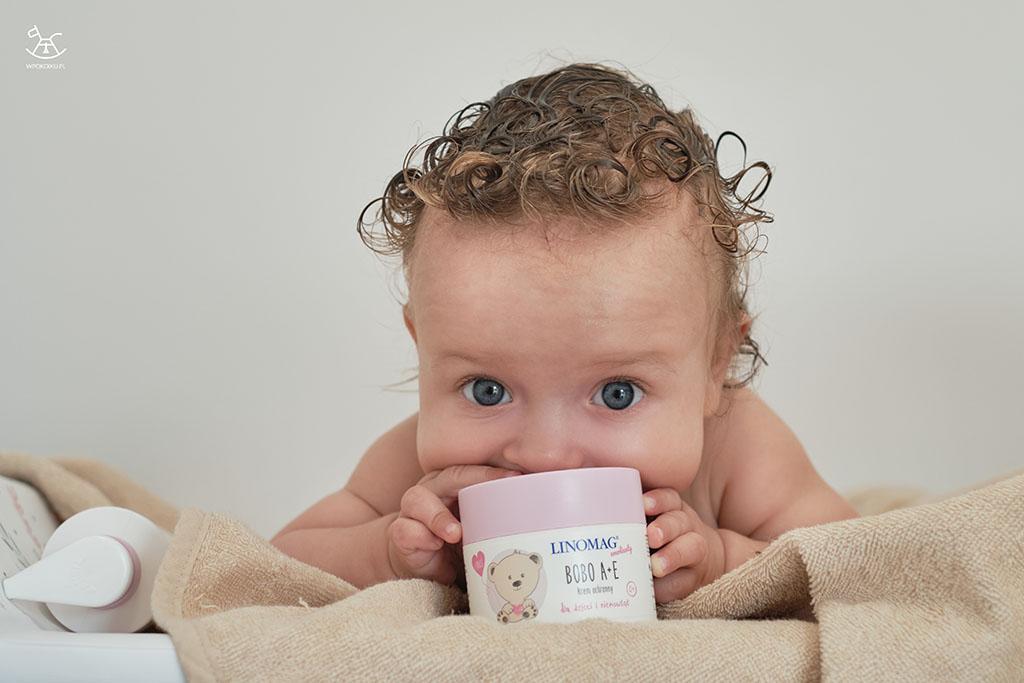 niemowlak opiera się o słoiczek z kremem