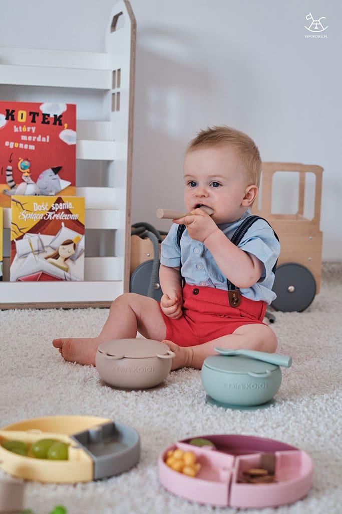 silikonowe akcesoria do karmienia i chłopczyk na dywanie w pokoiku