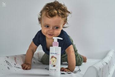 buteleczka mydła dla dzieci na przewijaku w tle uśmiechnięty chłopiec