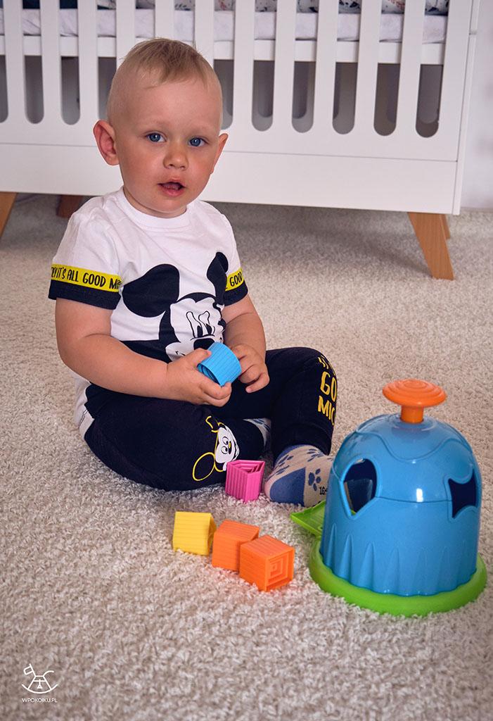 chłopczyk siedzi na dywanie z kolorowym domkiem sorterem i klockami
