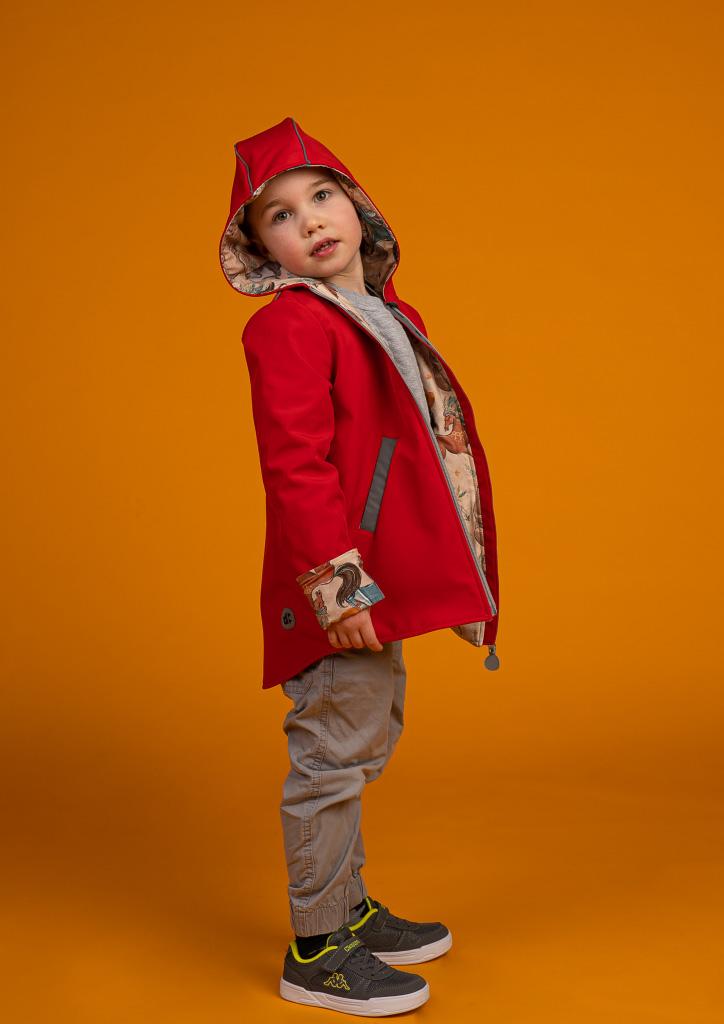 chłopiec stoi bokiem w rozpiętej kurtce z kapturem na głowie