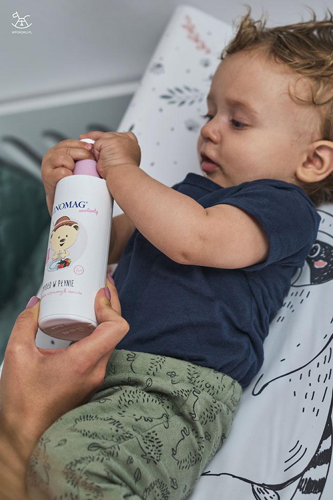 chłopiec trzyma butelkę z mydłem w płynie