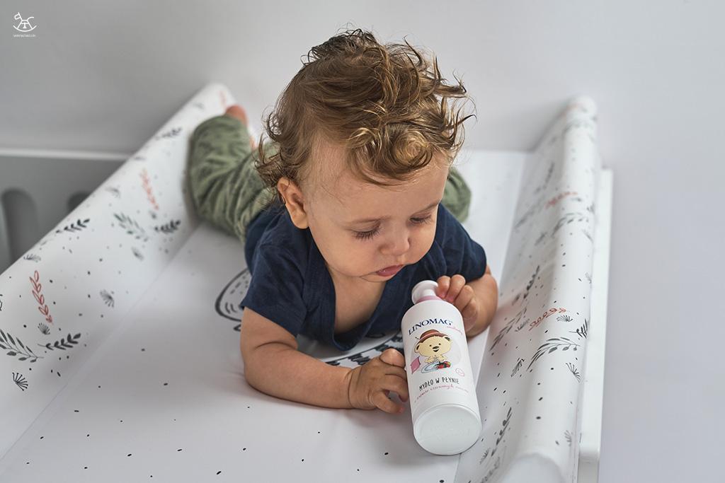 chłopiec trzyma w rączkach butelkę mydła w płynie dla dzieci