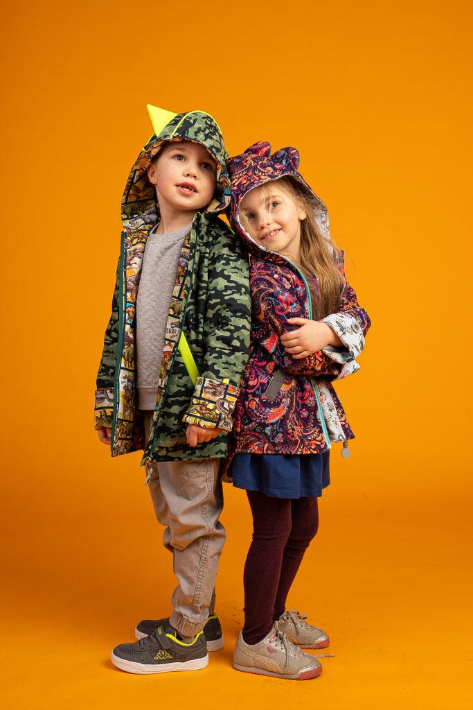 dzieci stoją oparte o siebie plecami w kurteczkach softshellowych z kapturami na głowach