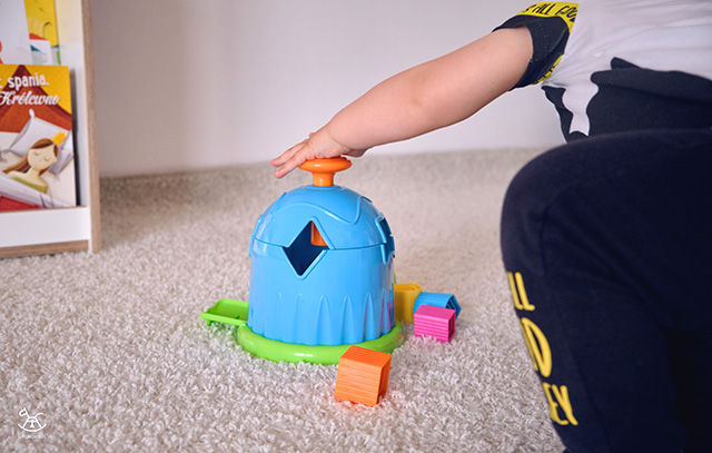 dziecko naciska przycisk na górze domku