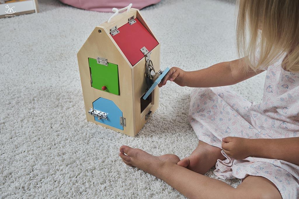 dziecko uchyla klapkę w drewnianym domku