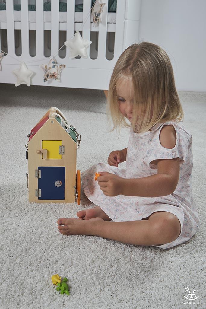 dziecko wyciąga z domku figurki dinozaurów