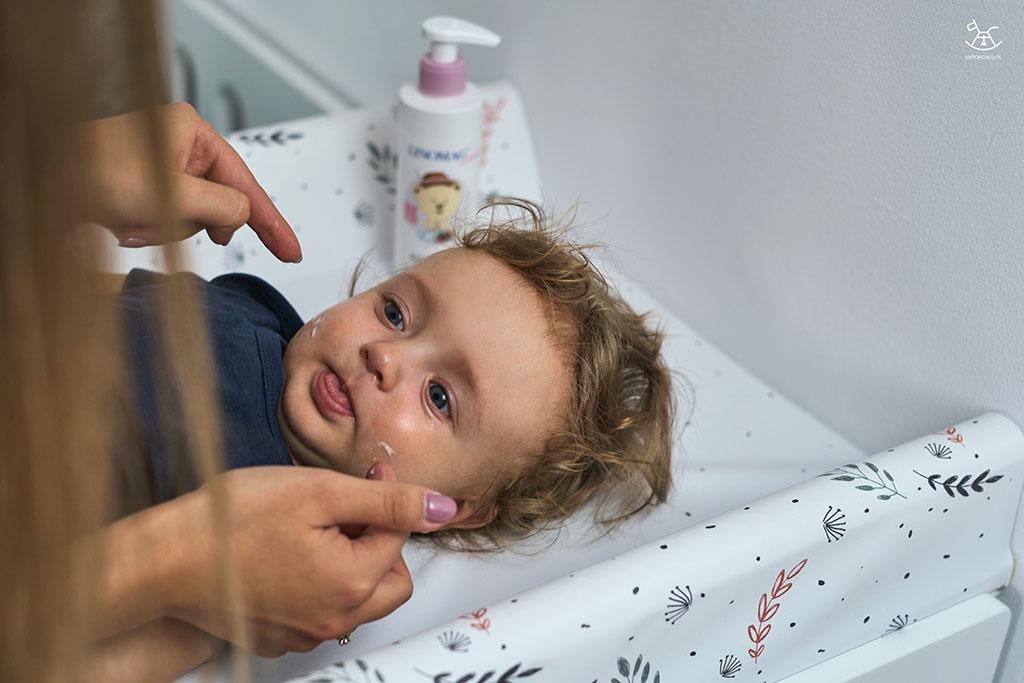 dziecko wystawia język podczas mycia buzi przez mamę