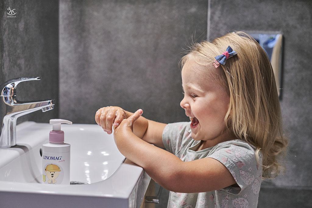 dziecko z radością myje rączki w łazience