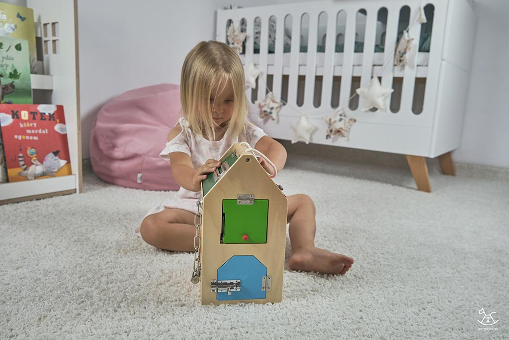 dziewczynka bawi się drewnanym domkiem na dywanie w pokoiku